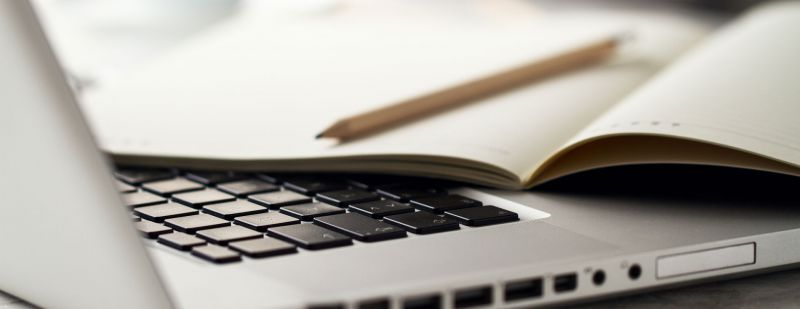 Computadora con un cuaderno encima.