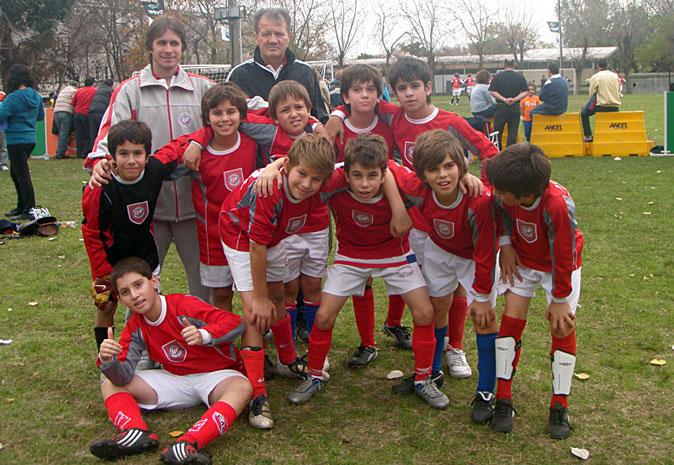 Grupo de niños en una cancha de fútbol.